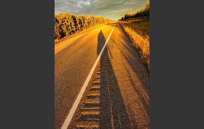 ハイウェイに沿って落ちる長い夕陽の影
