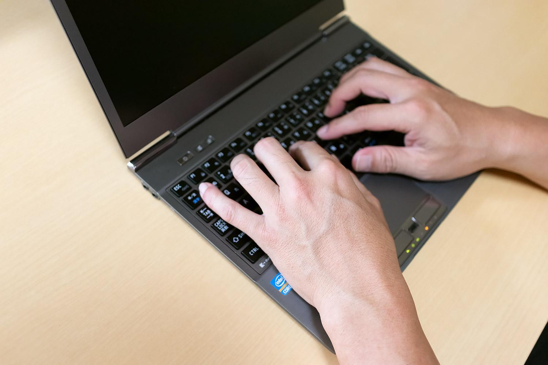 ノートパソコンのキーボードを打つ手(中年男性)