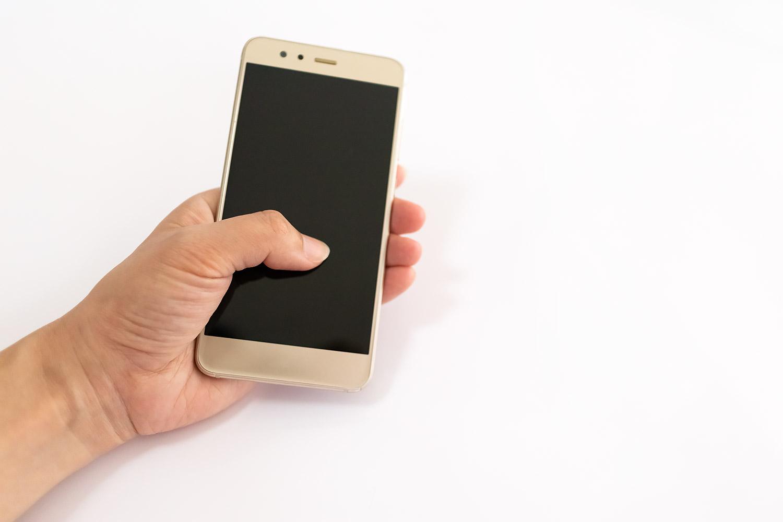 スマートフォンを片手で持って操作中(男性の手)