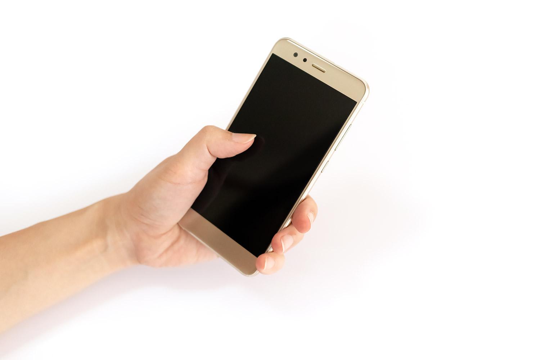スマートフォンを片手で持って操作中(女性の手)