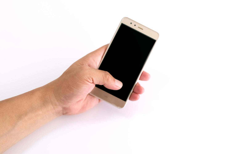 スマートフォンを片手で持って親指で押す(男性の手)
