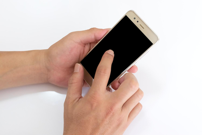 スマートフォンを両手で操作中の男性(右利き)